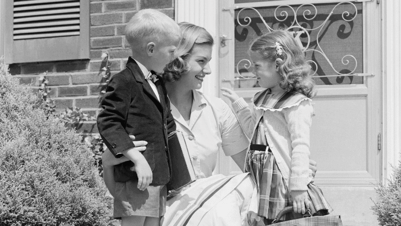 Quotes about homemaking help women like the one in this photo. She is kneeling down to be face to face with her children. One is a boy, dressed in a kid's suit. The other is a girl, her hair wavy. The mother is smiling. This is a vintage image from roughly the 1950s.