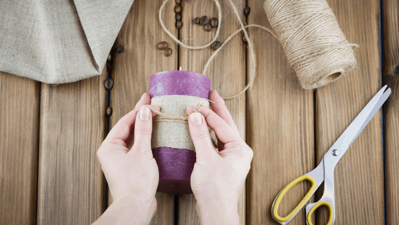 Decorative image of a woman tying together a candle wrapped in burlap. The purple candle is a beautiful example of aromatherapy candle making. There are sharp scissors, coffee beans, and burlap on a wooden table.