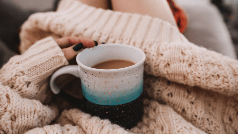 Why is hygge so popular? Because it nourishes our souls, like this warm cup of coffee and this oversized sweater.