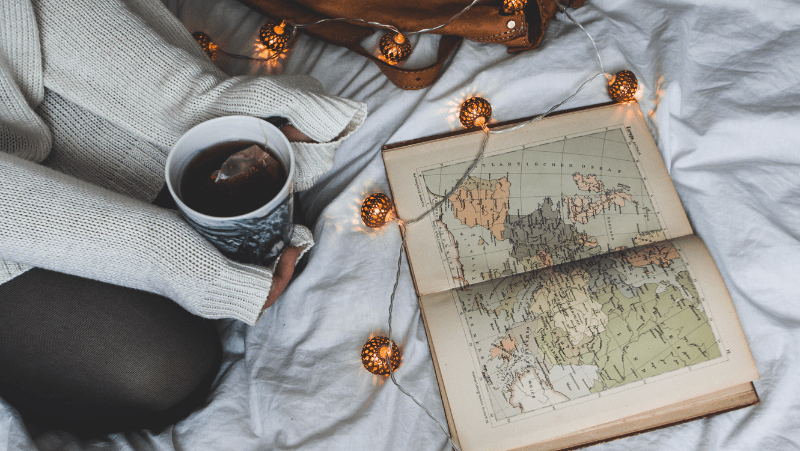 Decorative image of a woman in a white sweater, surrounded by eccentric string lights. She's holding a cup of dark tea and looking at a map of Europe in an old book.