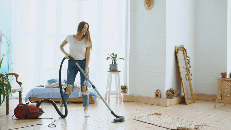 A woman testing vacuum cleaners in her clean, bright house