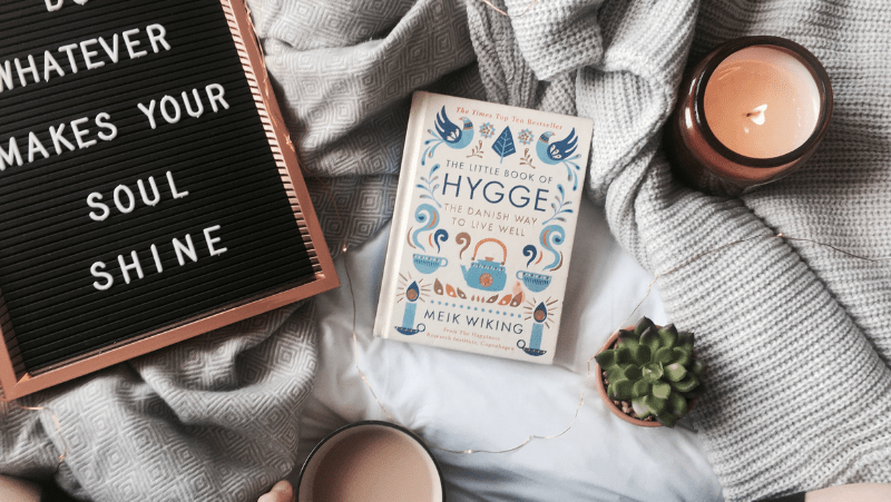 Decorative image of The Little Book of Hygge by Meik Wiking. It is sitting on a bed covered in blankets, candles, a succulent, a cup of coffee, and a cork board.