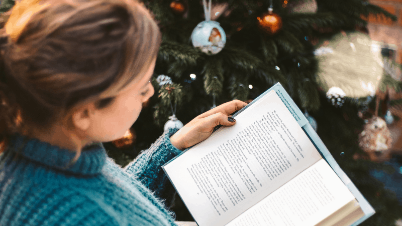 Decorative image of a woman with her hair in a pony tail. She is peacefully reading a hygge book by a decorated Christmas tree.