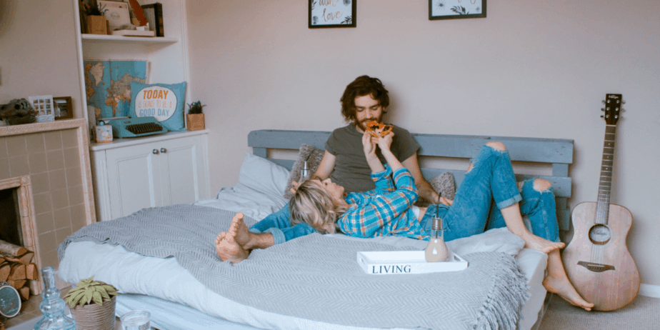 Decorative image of a husband and wife lounging on a bed and eating pizza. There is an acoustic guitar by the bed and interesting decor around the room. The wife is feeding her husband the pizza.