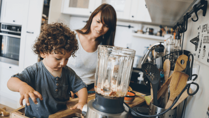 Decorative image of a mother and son making food in a blender in a messy kitchen