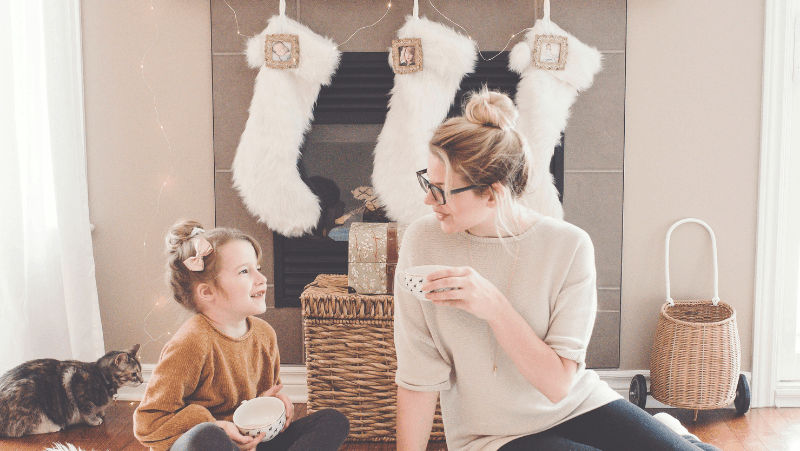Decorative image of a mother and daughter sitting in front of a fireplace. The fireplace is decorated with white stockings and wicker baskets. Behind the daughter is a tan and black cat. Mom and daughter are both drinking hot cocoa.