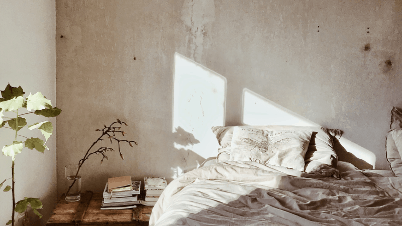 Decorative image of a minimalist but cozy bedroom. The bed is next to a trunk with many books on top of it. The sun is shining into the room.