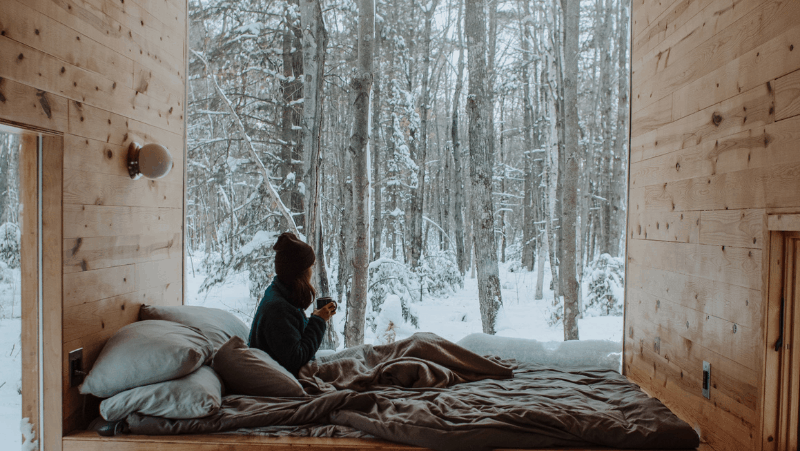 Decorative image of a woman sitting in front of a huge window looking out into a snowy forest. In front of the window is a bed with many plush pillows and brown blankets. The woman is wearing a brown beanie hat and drinking coffee.