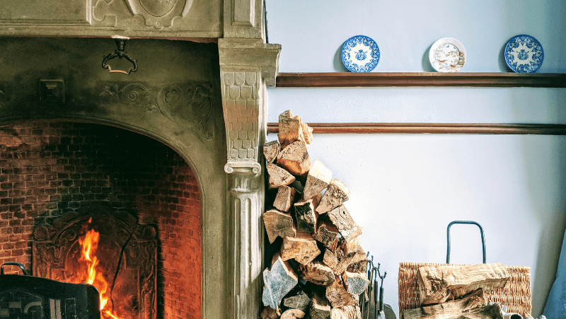 Decorative image of a fireplace and logs for the fire. On the wall is a few decorative plates.