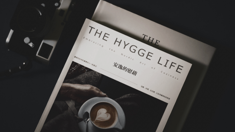 Decorative image of The Hygge Life, Embracing The Nordic Art Of Coziness. This is a Japanese book. Next to it is an old fashioned camera.
