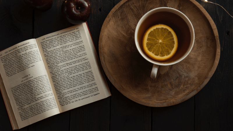 Decorative image of tea with a lemon slice in it, resting on a rustic wooden tray. Beside it is an old book and a dark red apple.