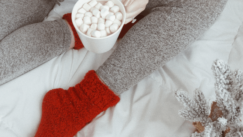 Decorative image of a woman wearing gray heather leggings, fuzzy red socks, and holding hot cocoa with a million marshmallows.