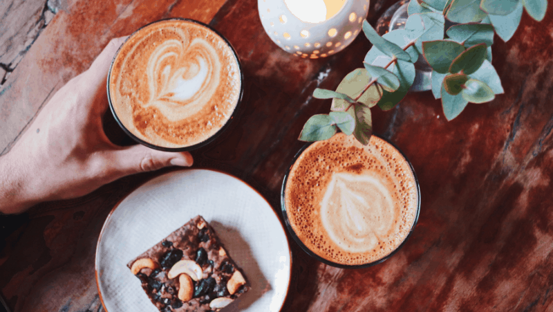 Decorative image of beautifully made coffee, a houseplant, and a brownie with nuts. Some of the nuts are arranged to look like a mushroom, and it's very cute.