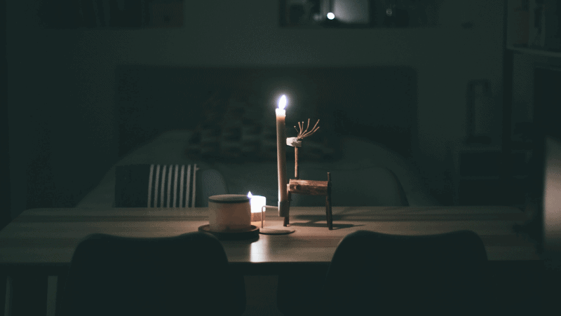Decorative image of a table with candles and a rustic, wooden reindeer decoration.