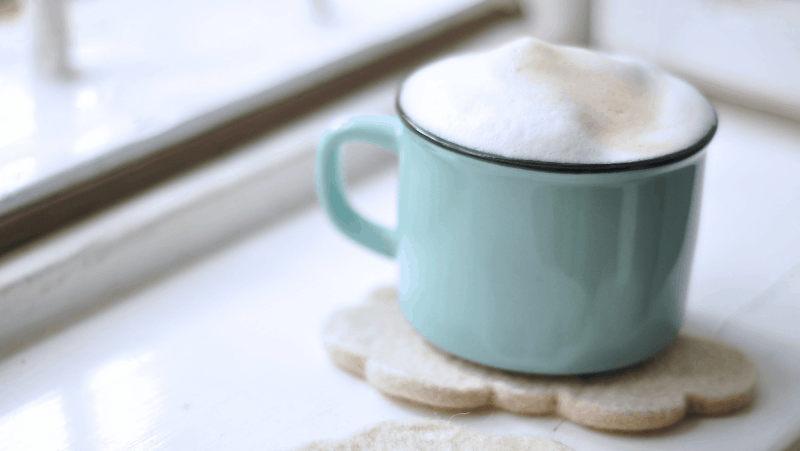 Decorative image of a coffee cup filled with a latte. It's on top of a cookie and on a windowsill.