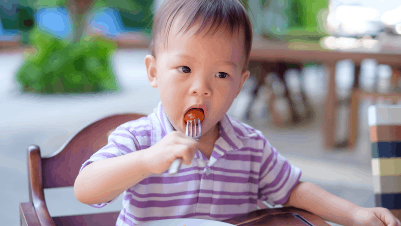 Decorative image of a toddler eating a tomato