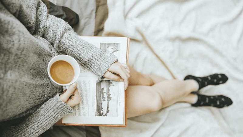 Decorative image of a woman reading a physical book with a cup of coffee. She is wearing dark socks and sitting on what looks to be a bed. The book seems to be a nonfiction book about history, as there are black and white photos of boats and houses.