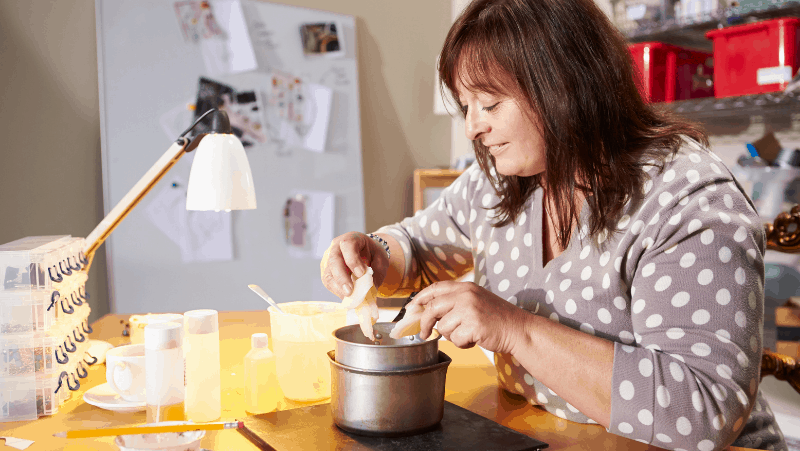 Decorative image of a woman melting wax to be made into an aromatherapy candle. She is smiling as she works because she loves her aromatherapy candle making hobby.