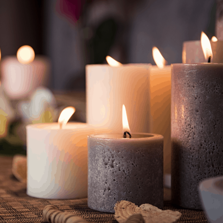Decorative image of lit candles in gray and white on a wooden table.