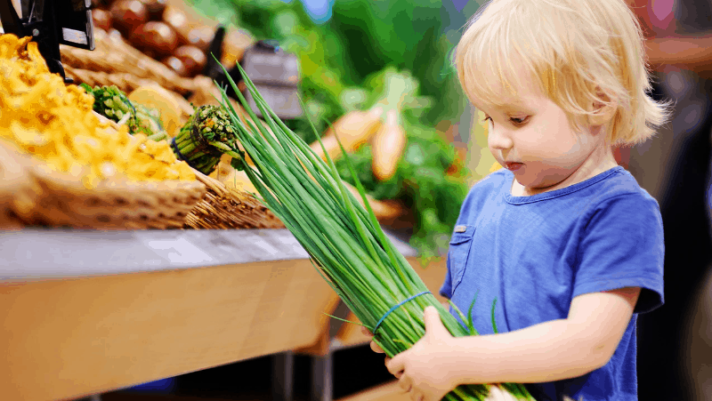 Decorative image of a toddler picking up vegetables from the grocery store
