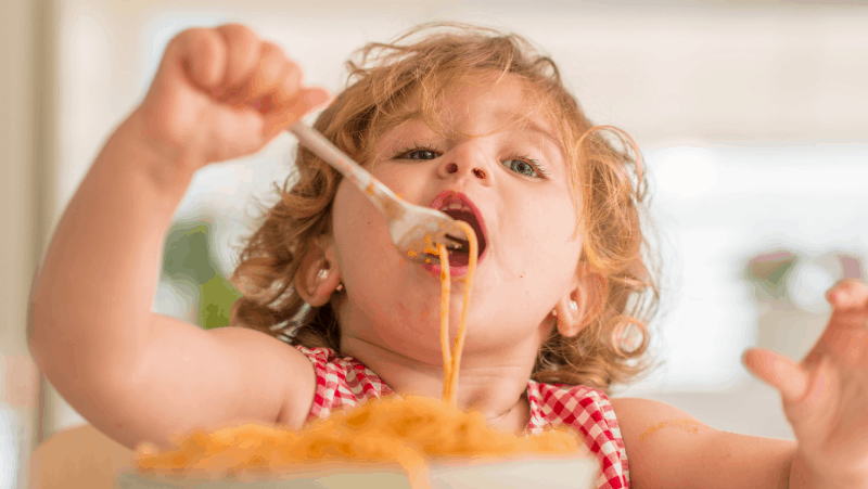 Decorative image of a toddler eating a long spaghetti noodle