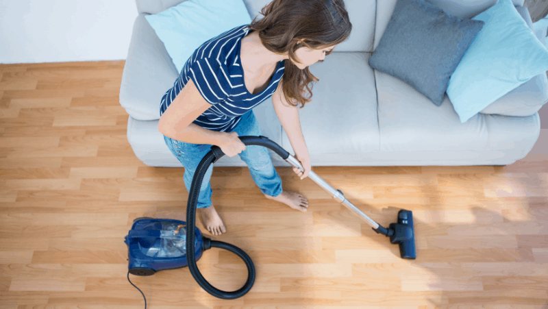 A woman vacuuming her hardwood floor next to a gray couch.