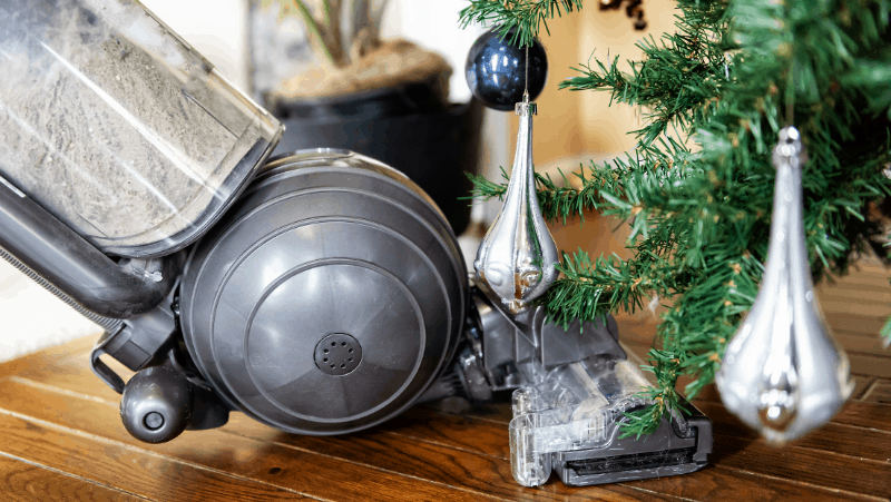 A vacuum on hardwood flooring under a decorated hygge Christmas tree.