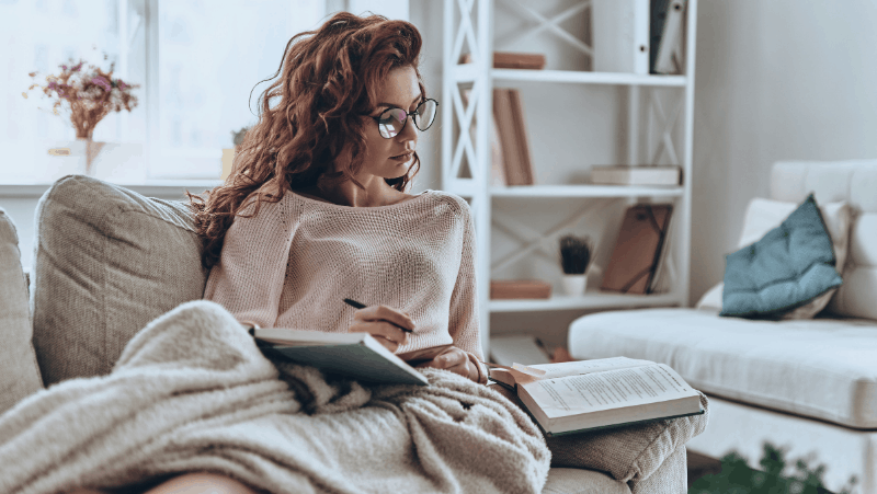 Decorative image of a beautiful red head sitting on a couch. She is embodying the hygge lifestyle as she reads a book and takes notes in her notebook. She's snuggled up with a comfy blanket and surrounded by beautiful decor.
