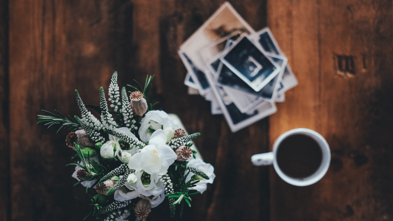 Decorative image of beautiful flowers and a cup of coffee next to a pile of photographs on a wooden table.