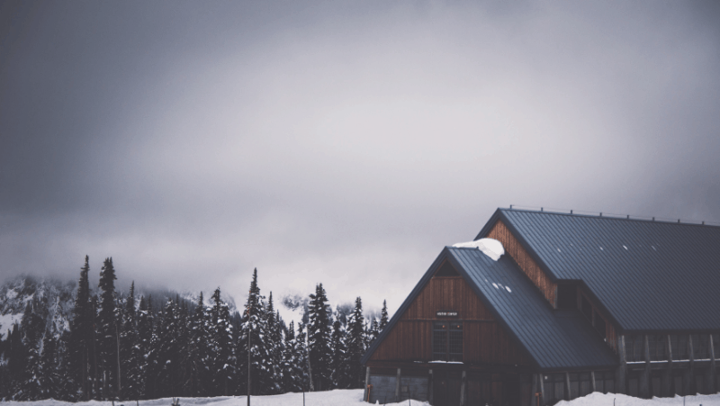 Decorative image of a snowy cabin on a hazy, gray day in winter.
