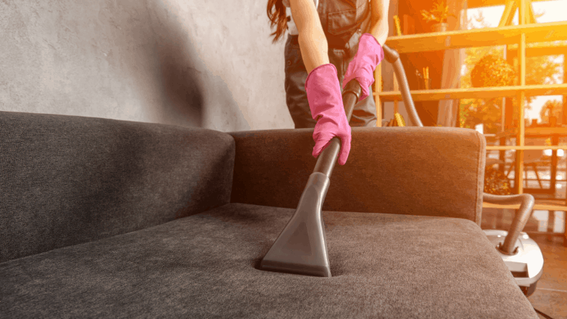 a woman with pink cleaning gloves using a vacuum's hose attachment to clean a dark gray couch as the sun sets.