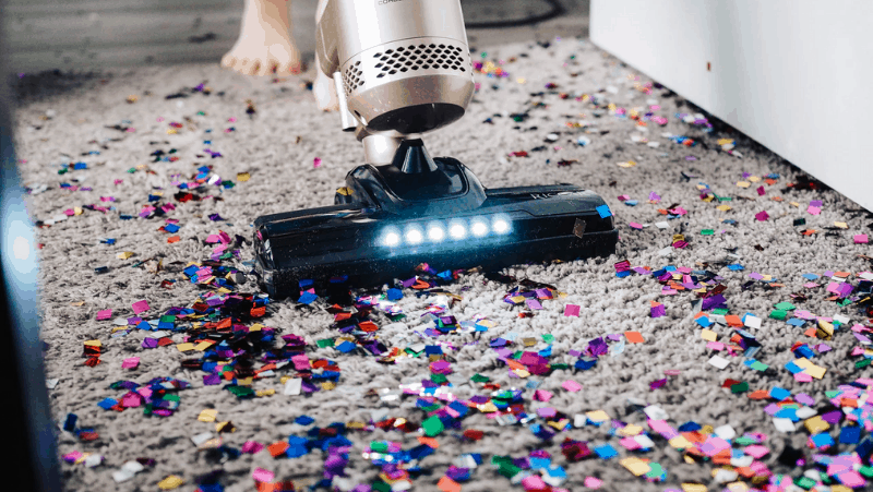 A vacuum with lights on its head is being used to vacuum up a LOT of confetti. That's way too much confetti. That's gonna take a while to clean up.