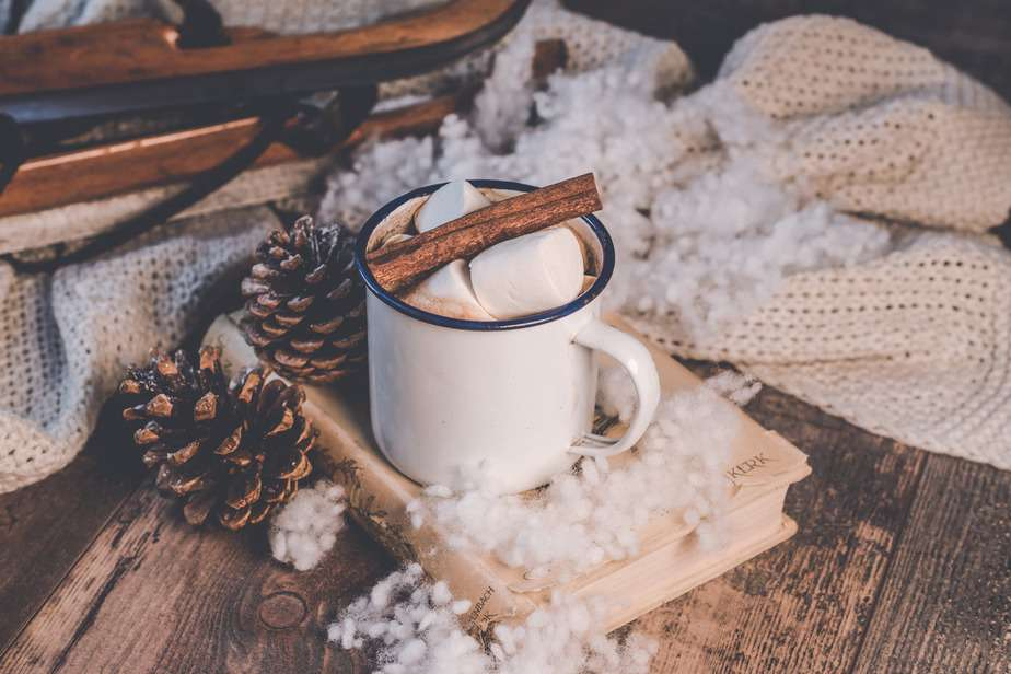 white ceramic mug. Hot chocolate and warm sweaters are part of the cozy Christmas aesthetic.