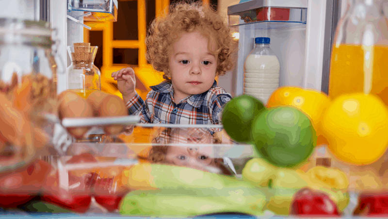 Decorative image of a toddler grabbing food from a full fridge